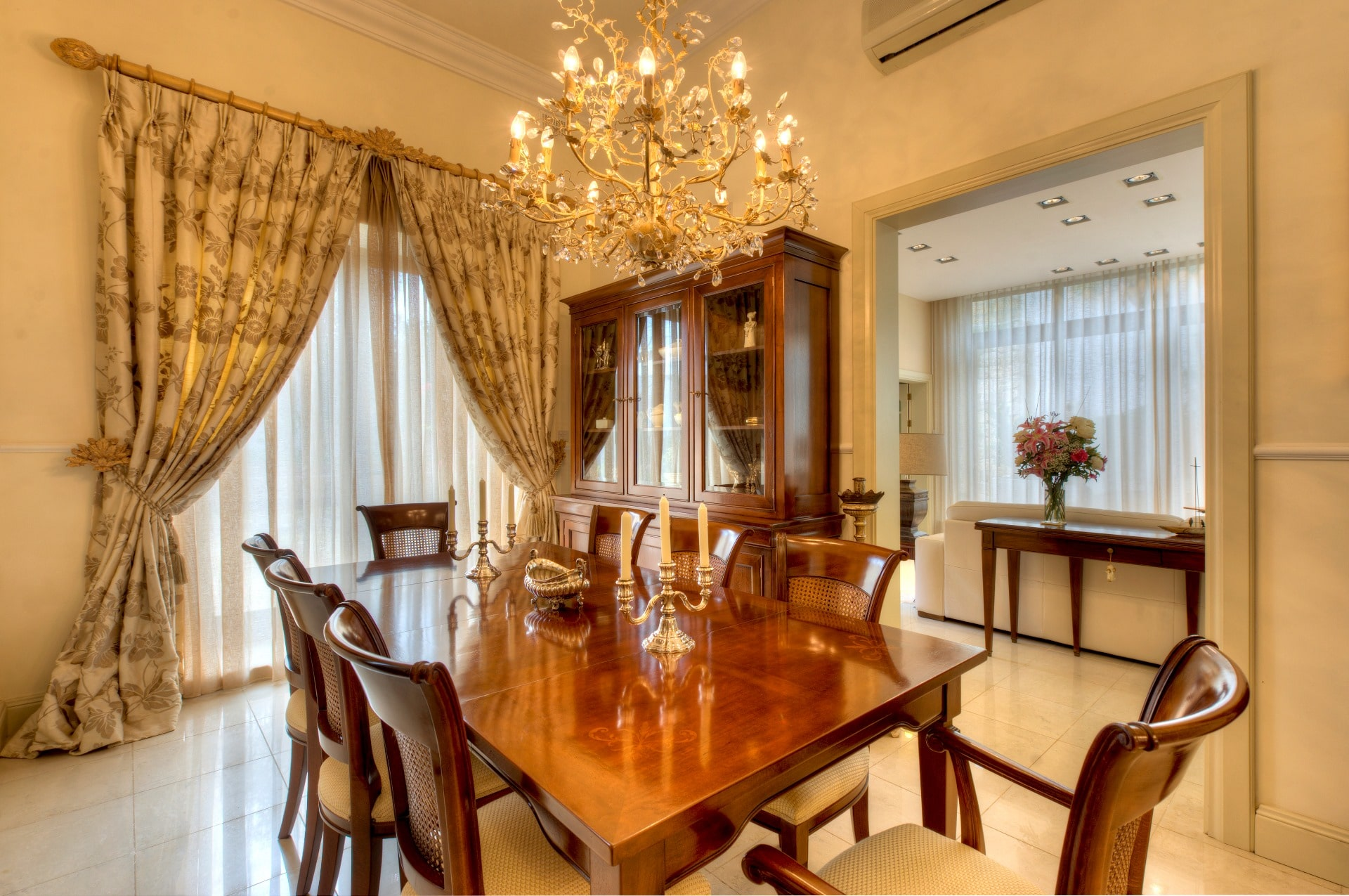 Dining Room – large table, antique chairs, gold tones, cream linens, marble floors, chandelier