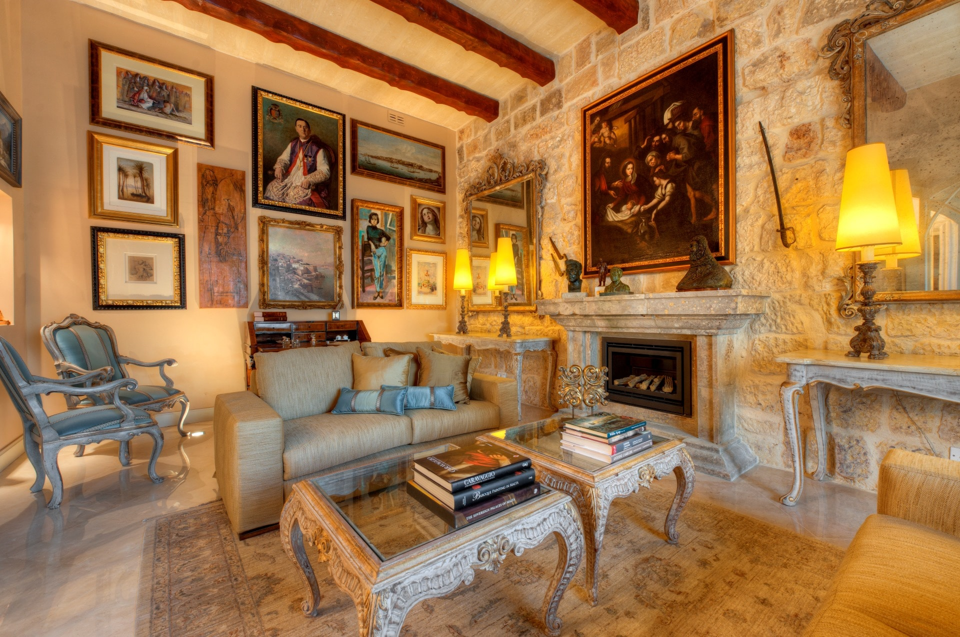 Entertainment Room – rustic stone fireplace, low sofas, antique gold, marble flooring