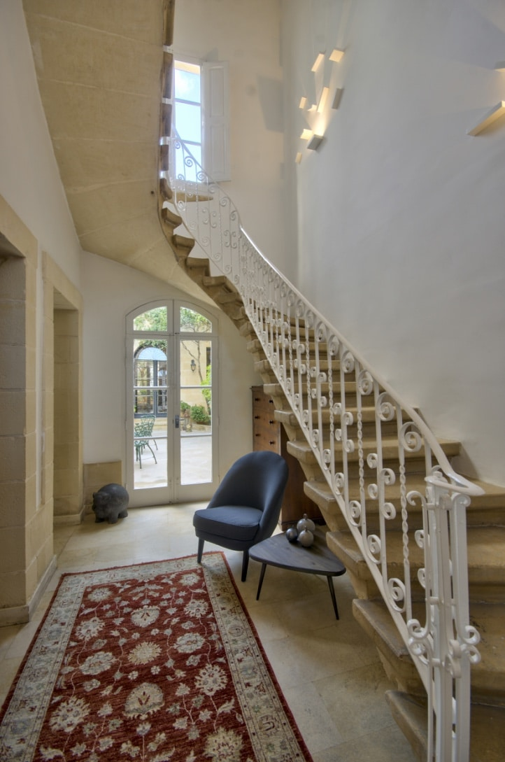 Hall – staircase, metal railings, sculptural wall lights, seating area